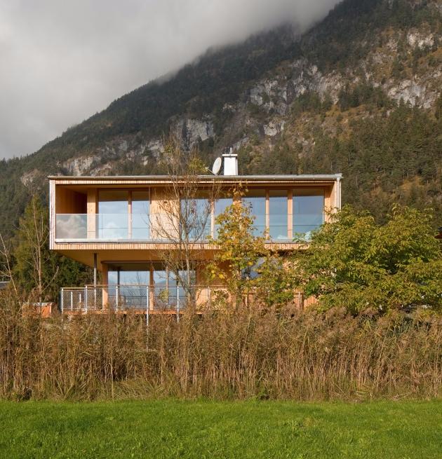 Modernes Holzhaus mit Schilfgürtel im Vordergrund und Berg im Hintergrund