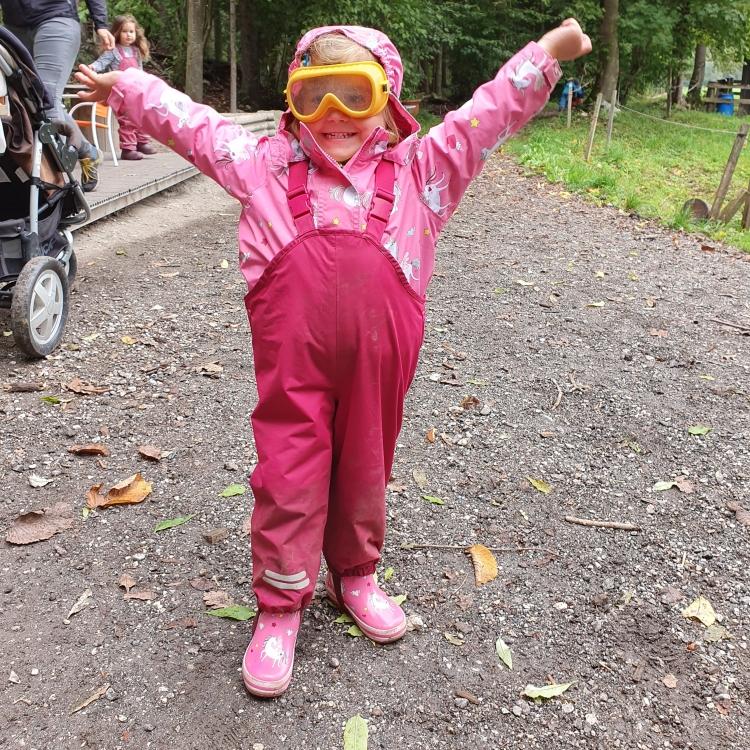 Kind mit Matschanzug und Taucherbrille im Waldkindergarten
