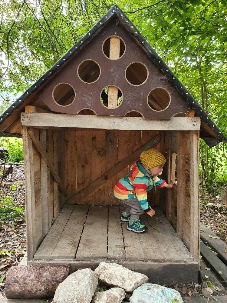 Kind in kleinem Haus im Waldkindergarten